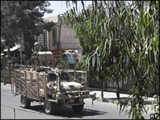Veículo militar da Otan cruza rua de Candahar durante confrontos deste sábado (AP)