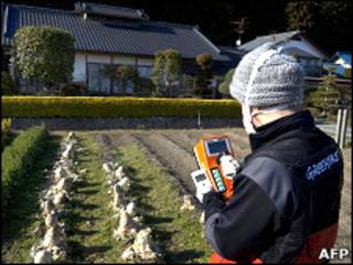 Especialista da ONG Greenpeace monitora níveis de radiação em lavoura na região de Fukushima (Foto: Christian Aslund/ Greenpeace/ AFP)
