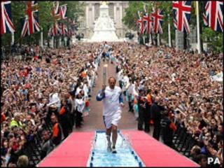 Campeão olímpico britânico Steve Redgrave carrega a tocha olímpica durante trajetória da tocha nos jogos de 2004 (PA)