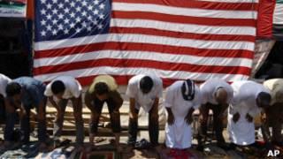 Líbios rezam diante de bandeira americana em Benghazi. AP