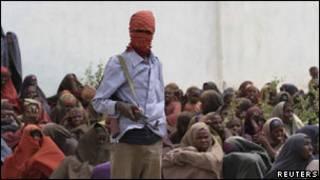 Боевик Аль Шабаб наблюдает за раздачей еды в Сомали