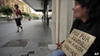 Mulher desempregada pede ajuda em Madri, em foto de julho (AP)