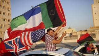 Militante rebelde celebra fim do regime, em Benghazi. AP