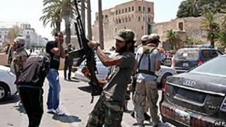 Rebeldes líbios comemoram disparando para o alto em Trípoli (AFP)