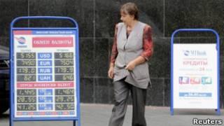Женщина проходит мимо щитов с курсами валют