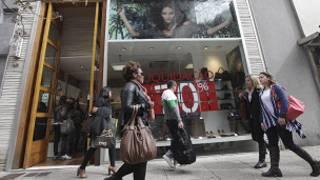mulheres passam em frente a loja   Foto: AP