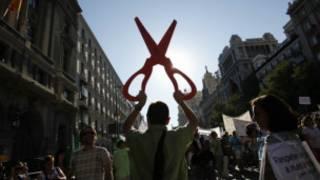 Un hombre empuña una tijera gigante en una manifestación contra los recortes en España