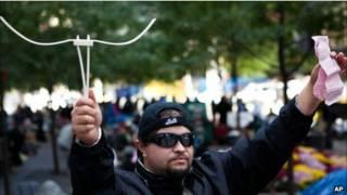 Người tham gia biểu tình Michael Pellagatti ở New York cầm còng tay bằng nhựa mà cảnh sát dùng để khống chế ông cùng trát của tòa án
