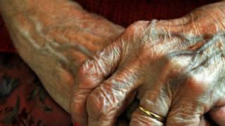 Mão de senhora idosa em casa de repouso em Londres. PA