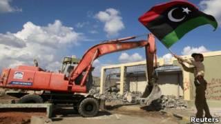 Бульдозер сносит здание под флагом новой Ливии