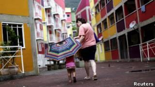 Moradora caminha com criança na Rocinha (Foto: Reuters)
