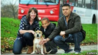Pat Oates com o cachordo T-Bone ao lado do companheiro e do neto em frente ao ônibus no qual ele foi encontrado