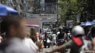 Pedestres e motociclistas em rua da Rocinha, no Rio (Foto: Reuters)