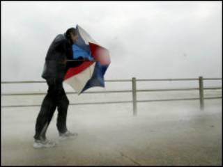 一名男子在肯特郡某地海边顶风前进
