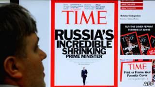 Мужчина рассматривает на экране обложку журнала Time с Путиным