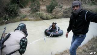 Membros do Exército Livre Sírio transportam remédios e armas por um rio em Idlib.   Foto: AFP