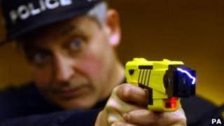 Policial usando arma 'taser'