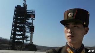 Soldado norte-coreano monta guarda próximo ao foguete lançado na quinta-feira. | Foto: AFP