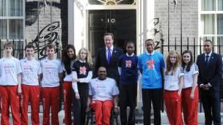 英国首相卡梅伦在唐宁街10号门前与奥运志愿者代表合影