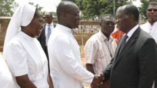 Le président Ouattara serrant la main du père Cyprien Ahore à Duékoué.