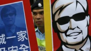 Policial entre dois cartazes com rosto de Chen (AP)
