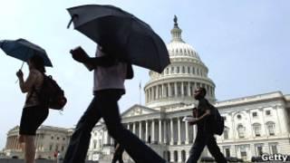 Туристы в Вашингтоне скрываются от солнца под зонтами