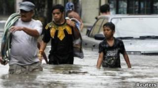 Жители Манилы, половина которой оказалась затопленной в результате наводнения