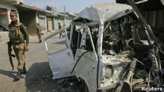 Полицейский у взорванной машины в пакистанском городе Дарра Адам Хель