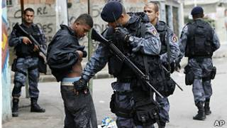 Бразильский полицейский обыскивает задержанного