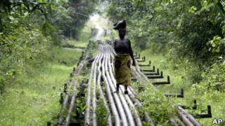 Mujer camina sobre conducto de petróleo en Nigeria