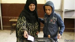 Una señora vota junto a su nieto