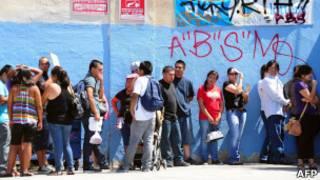 Inmigrantes en fila para entregar solicitudes