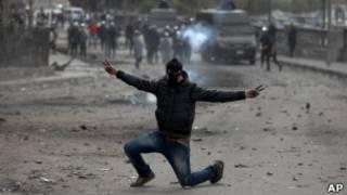 Individuo enmascarado hace el signo de la victoria en mitad de unos disturbios