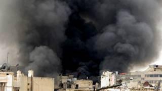 Дым над зданием в Алеппо после обстрела сирийскими правительственными войсками