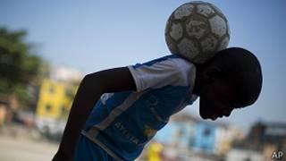 un niño hace equilibros con una pelota sobre la nuca