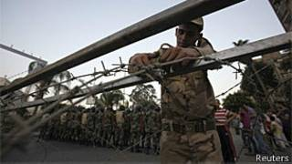 Militar coloca arame farpado enquanto soldados tomam posições em frente a manifestantes no Cairo (Reuters)