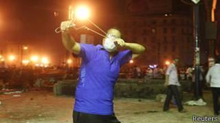 Un manifestante lanza una piedra