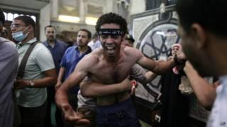 Egípcios contêm homem que lamenta a morte de parentes em uma mesquita no centro do Cairo / AP