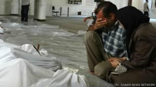 casal chora ao lado de vítima de ataque da quarta-feira | AFP