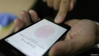 Dedo presiona el botón de inicio del nuevo iPhone 5S