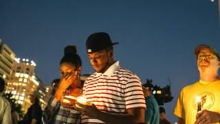 गोलीबारी में मारे गए लोगों के प्रति शोक जताते लोग