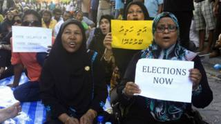 Женщины с плакатами сидят на дороге в Мале