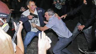 PM Reynaldo dos Santos sendo salvo por seu motorista armado de manifestantes. Foto: Reuters