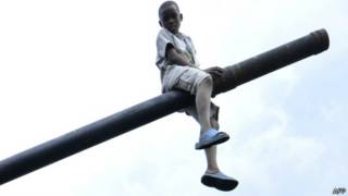 Criança brinca em tanque na República Democrática do Congo. Foto: AFP