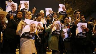 Iranianos foram para o aeroporto com fotos do presidente Hassan Rouhani (AP)