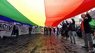 Manifestantes con una bandera del orgullo homosexual