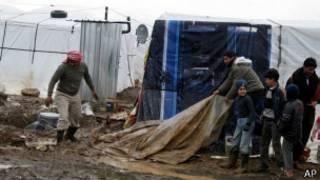 لاجئون يحاولون حماية خيمهم من الأمطار