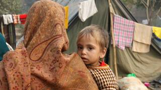 राहत शिविर में रह रही महिला अपने बच्चे के साथ