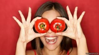 Foto de mujer haciendo una gracia con dos tomates.