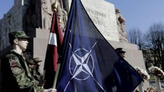 नाटो का झंडा थामे लातविया का सैनिक